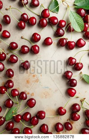 Freshly picked cherries with stem and leaves on table