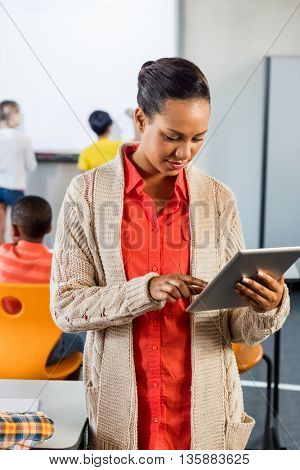 Portrait of a teacher using tablet pc in class at elementary school
