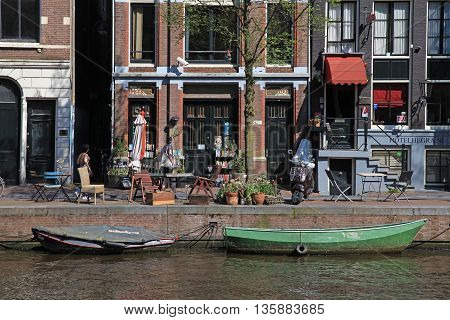 AMSTERDAM, NETHERLANDS -MAY 8, 2016: Beautiful view with traditional dutch houses along waterfront of canals in Jordan district Amsterdam, the capital of the Netherlands.