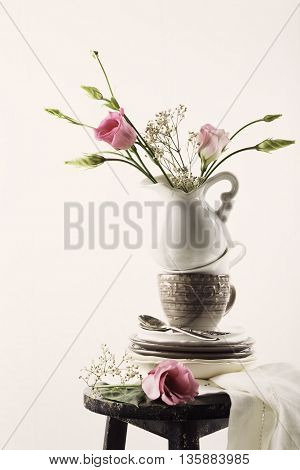 Tableware with flowers. Plates, coffee cups, a pitcher of pink flowers on an old black stool. Consept with copy space for text. Toned.