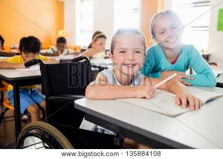Two smiling pupils posing for the camera in classroom