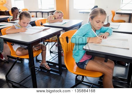 Pupils studying at at their desk in classroom