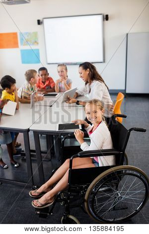 Cute girl in wheelchair posing for the camera in classroom