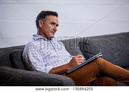 A businessman writing in a notebook on sofa