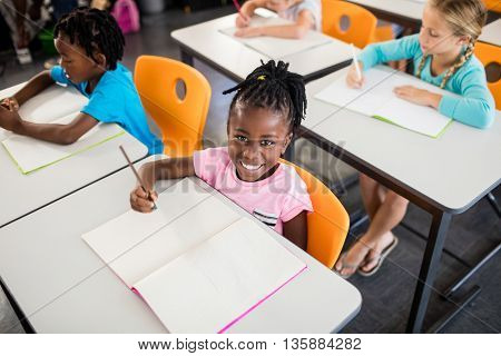 A cute girl sitting at desk looking at the camera in classroom