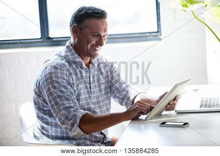 Smiling man working at desk with tablet in office