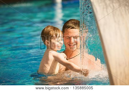 Father playing with his little son in pool