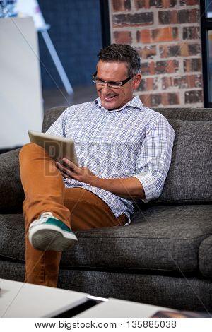A businessman using digital tablet in sofa