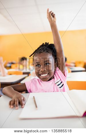 A cute pupil raising hand in classroom