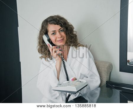 Portrait of young curly woman in white bathrobe using phone in hotel room and looking at camera.Young lady call to reception. Room service with phone