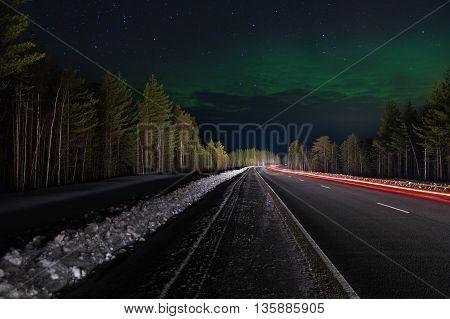 Aurora over the highway running through the woods