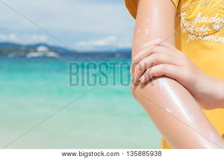 young girl applyng sun protector cream on her hand on the beach close to tropical turquoise sea under blue sky at sunny day