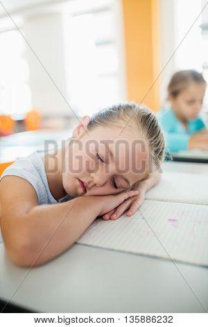 A cute girl falling asleep at desk in classroom