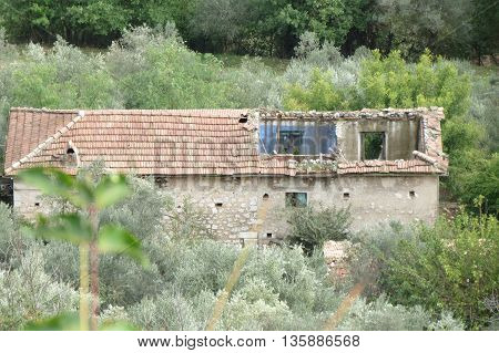 Ruined house without a roof and walls severely damaged
