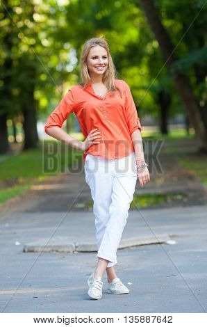 Portrait Of Young Smiling Beautiful Woman. Attractive young woman enjoying her time outside in park with sunset in background.