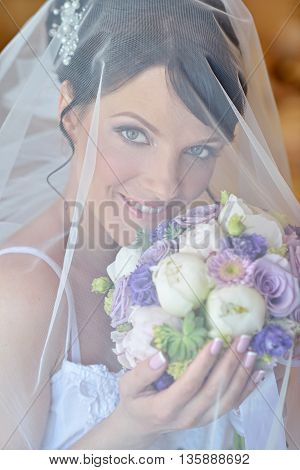 Beauty Bride In Dressing Gown With Bouquet And Lace Veil Indoors. Beautiful Model Girl In Colorful W