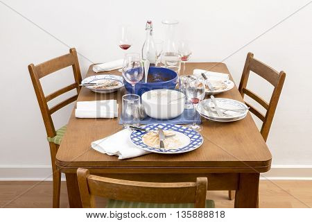 Table with chairs and dirty dishes arranged on it