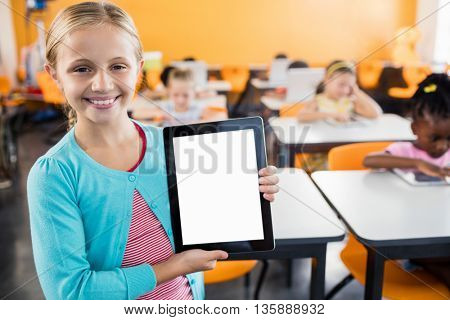 portrait of smiling pupil standing with tablet pc in classroom