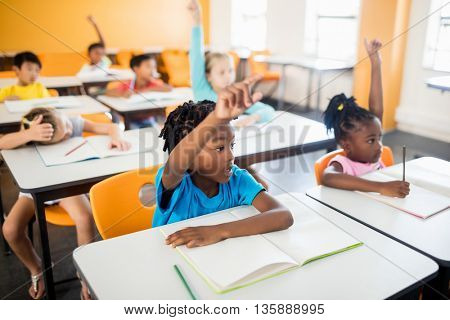 Pupils raising their hands in classroom
