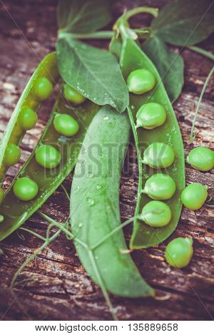 green peas on a brown ancient wooden table