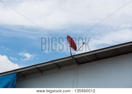 Red Satellite dish on the roof with a beautiful blue sky.