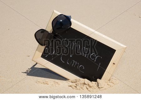 Chalkboard With The Text Summer Time On Sand Of Beach