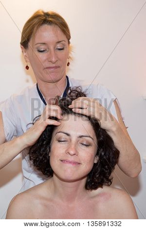 Smiling Woman In Spa Salon Receives Head Massage