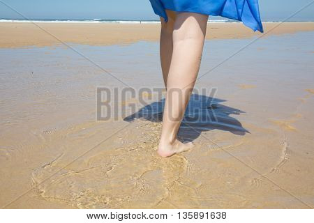 Young Woman Walks Alone On A Beach