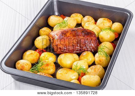 Oven Baked new potatoes with sea salt red bell pepper and pork tenderloin in a baking dish on a wooden table close-up