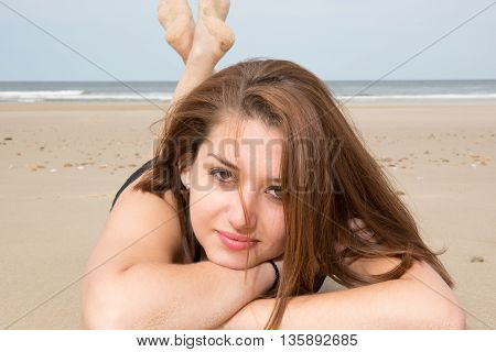 Smiling Young Woman Laying On Beach And Looking At Camera