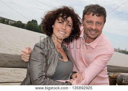 Cheerful And Happy Couple At River Cuddling And Have Fun