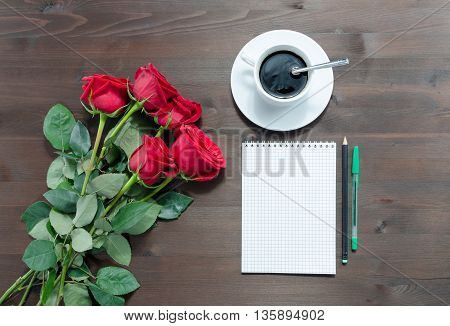 notebook pens cup of coffee and red roses on table