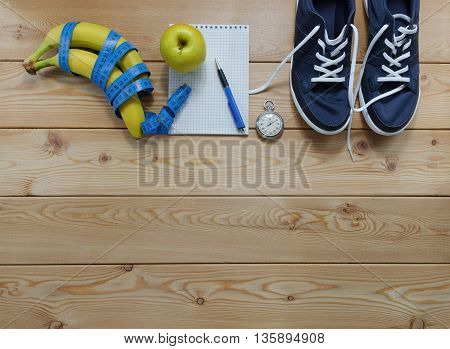 Fitness concept with sneakers. towel bottle of water measure tape fruit and a stopwatch.