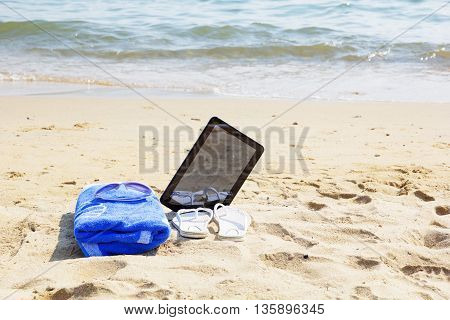 Sunglasses Tablet PC and Beach Towel on the Beach. Summer Vacations Concept.