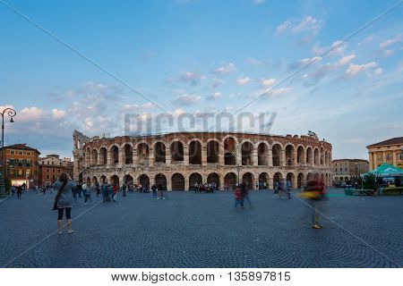 Verona Italy - May 07 2016: Some people walking on the Bra square against the backdrop of the Verona Arena evening time