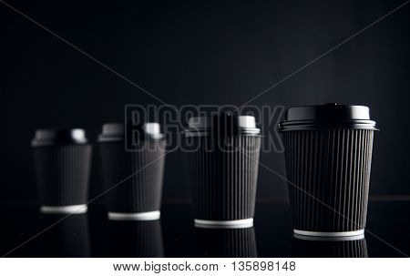 Luxury set of four take away cardboard paper cups closed with caps isolated on black and mirrored. Retail mockup presentation