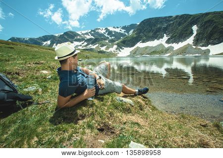 Traveler Man relaxing alone Travel Lifestyle concept lake and mountains sunny landscape on background outdoor