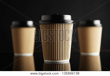 One focused in front of unfocused brown take away cardboard paper cups closed with caps isolated on black and mirrored. Retail mockup presentation