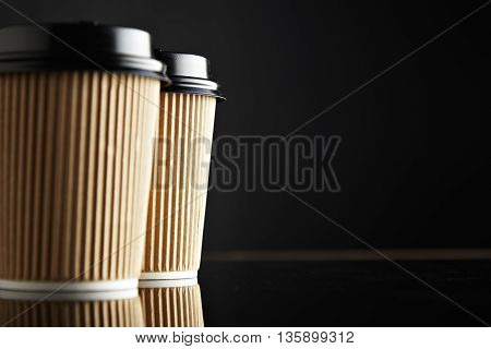 Brown take away paper cups closed with caps isolated on left, black background and mirrored image. Retail mockup presentation