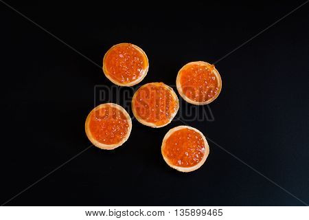 Round tartlets with russian red caviar on a black background