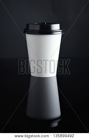 One take away white cardboard paper cup closed with caps isolated on black and mirrored. Retail mockup presentation