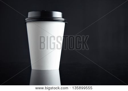 One take away white cardboard paper cup closed with caps isolated on left side and mirrored. Retail mockup presentation
