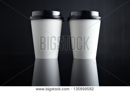 Two take away white cardboard paper cups closed with black caps isolated in center and mirrored. Retail mockup presentation