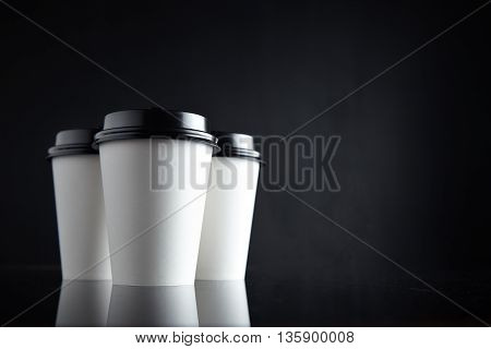 Set of three take away white coffee cardboard paper cups closed with black caps isolated on side and mirrored. Retail mockup presentation