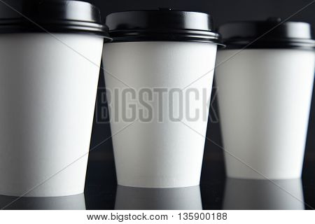 One focused paper cup for hot drinks between two unfocused presented on black back and mirrored, closed with caps, close focus mockup