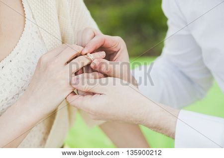 The offer to marry. Hands of the man dressing a ring on the beloved's finger. Hands of the man and woman. Golden Ring. Engagement.