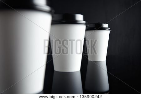 One focused paper cup for hot drinks behind two unfocused presented on black back and mirrored, closed with caps