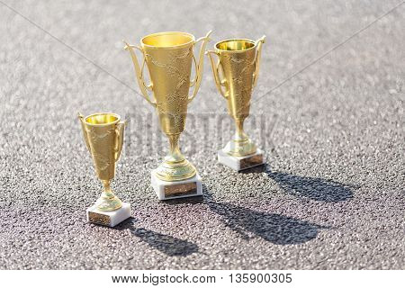 Trophy cups on asphalt. Three gold cups. Cups for a victory in sports competitions.