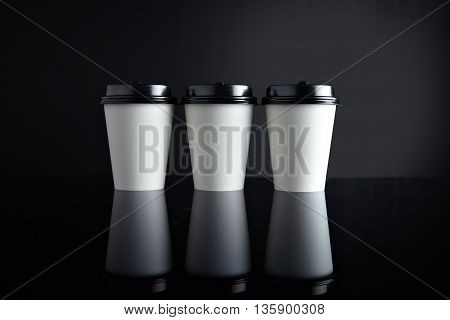 Three focused take away white paper cups for hot beverages closed with black caps isolated in center and mirrored. Retail mockup presentation