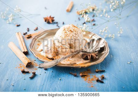 Scoop of homemade ice cream with cinnamon, apple syrup and spices on metal plate on blue wooden background. Summer food concept.